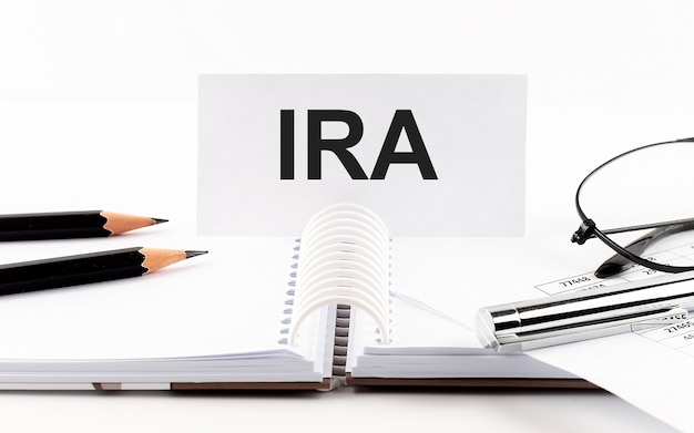 종이 카드, 펜, 연필, 안경 및 재정 문서에 ira 문자를 테이블에 표시합니다.