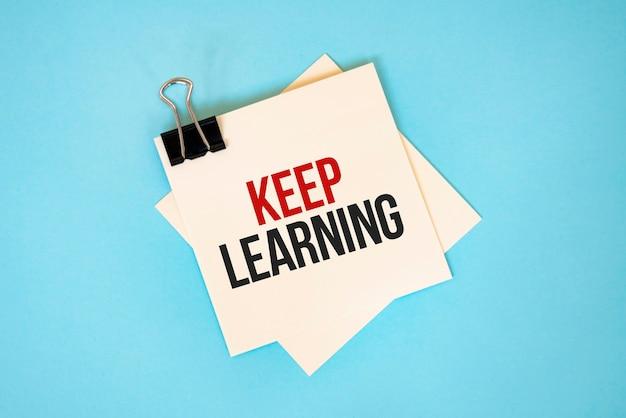 텍스트 복사 공간과 빨간색 배경에 고립 된 종이 클립 스티커 메모에 계속 학습 금융 및 경제 개념입니다.