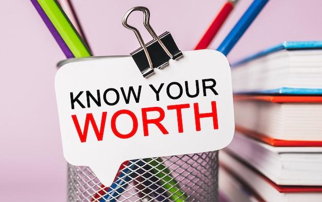 사무용 문구류가있는 흰색 스티커에 'know your worth'텍스트
