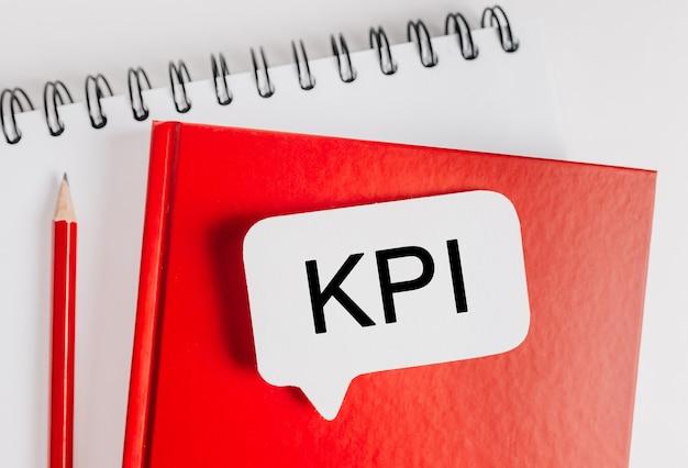 텍스트 kpi는 사무실 문구 배경이 있는 빨간색 메모장에 흰색 스티커입니다. 비즈니스, 금융 및 개발 개념에 평면 누워