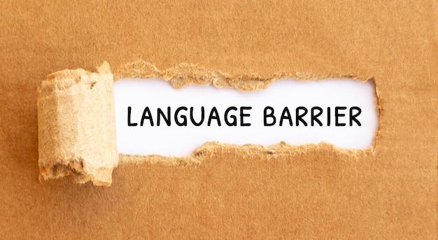 破れた茶色の紙の後ろに現れるテキスト言語の壁。