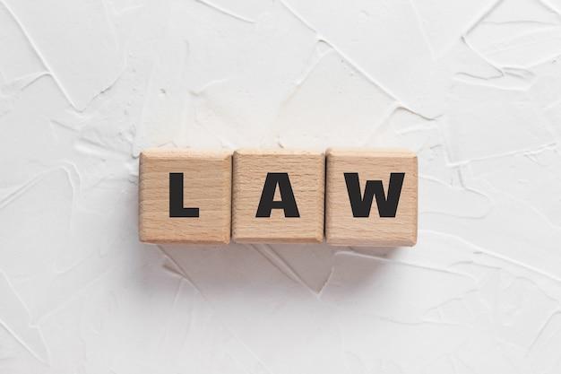 Текст закон сделан из деревянных кубиков на белом текстурированном фоне замазки. квадратные деревянные блоки. вид сверху, плоская планировка.