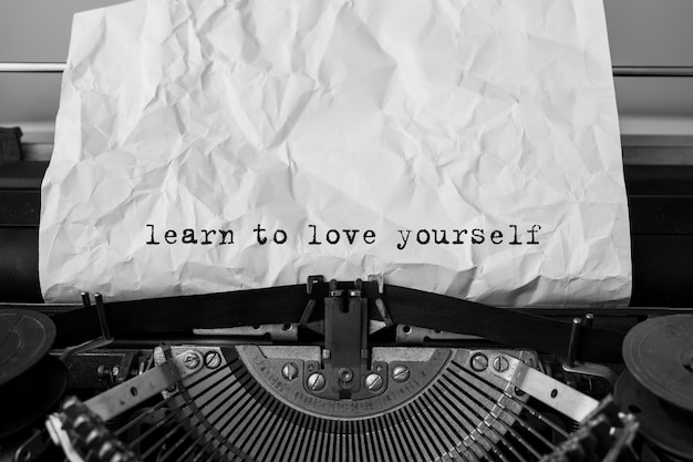 Text learn to love yourself typed on retro typewriter
