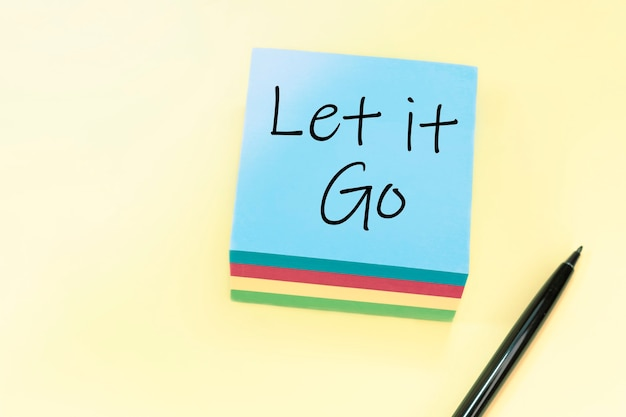 Текст let it go, написанный от руки черной ручкой на синем стикере.