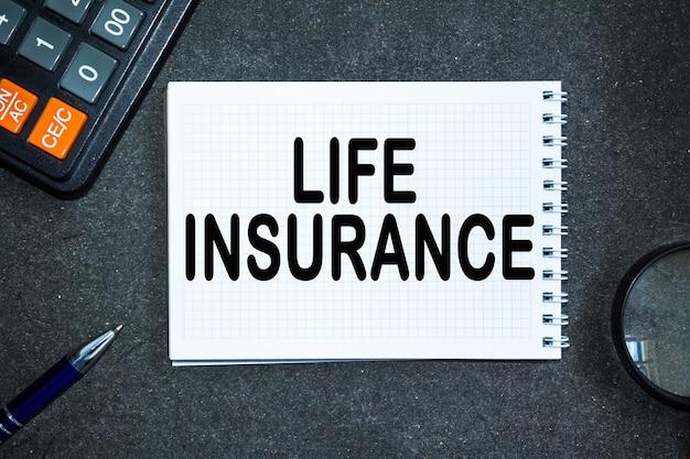 Текст страхование жизни. офисный стол, калькулятор, блокнот с документами. бизнес-концепция