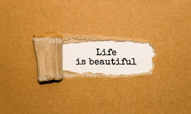 The text life is beautiful appearing behind torn brown paper