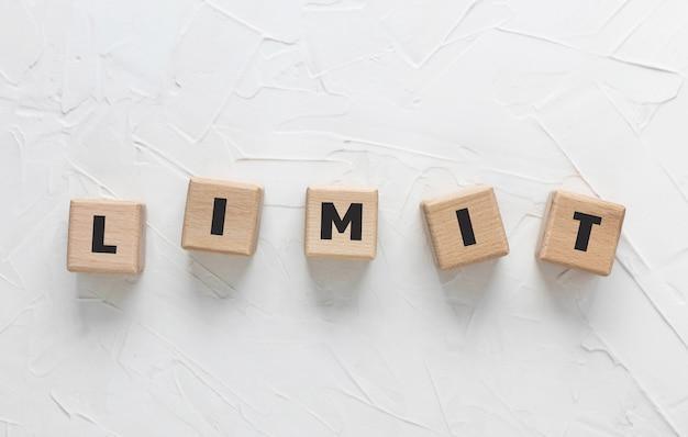 Текст limit сделан из деревянных кубиков на белом текстурированном фоне шпатлевки. вид сверху, плоская планировка. квадратные деревянные блоки.
