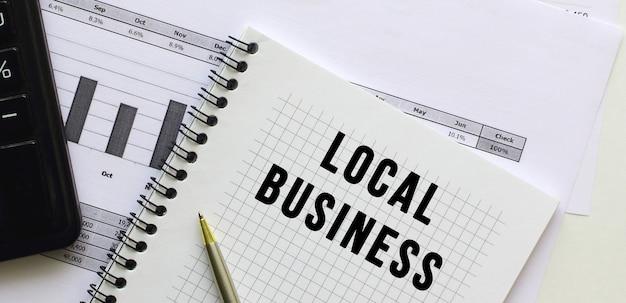 사무실 책상의 재무 차트에있는 메모장 페이지에 local business라고 문자를 보냅니다. 계산기 근처.