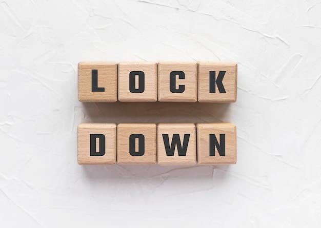 Текст lock down сделан из деревянных кубиков на белом текстурированном фоне шпатлевки. ограничения на поездки, связанные с пандемией covid-19. социальное взаимодействие. концепция коронавируса.