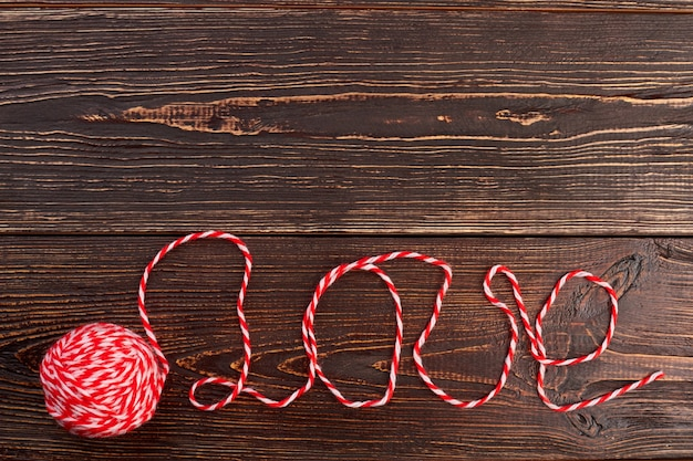 Text love written with woolen thread. ball of yarn for knitting and word love, copy space. love message concept.