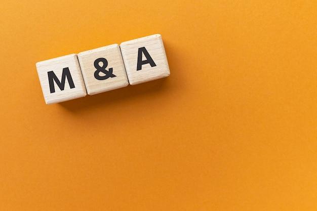 合併と買収の木製の立方体の略語のテキストma