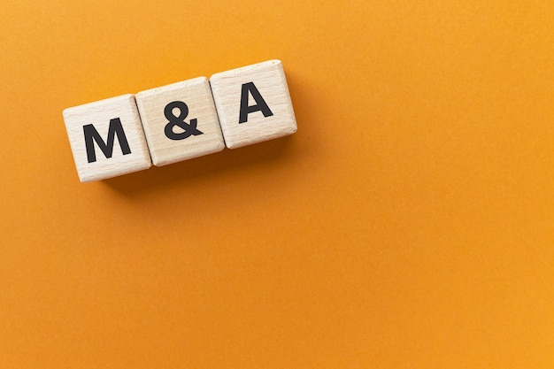 Text ma on wooden cubes abbreviation of mergers and acquisitions
