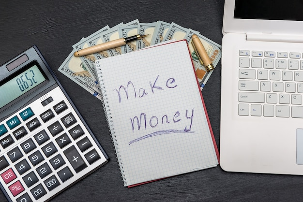 Text 'make money' with dollars, laptop and calculator