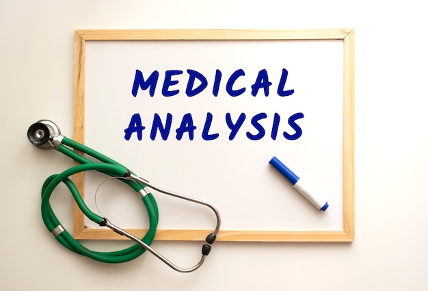 The text medical analysis is written on a white office board with a marker. nearby is a stethoscope. medical concept.