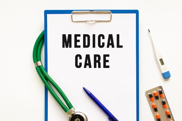 Text medical care in the folder with the stethoscope. medical concept photo