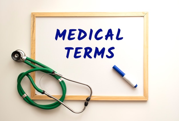 The text medical terms is written on a white office board with a marker. nearby is a stethoscope. medical concept.