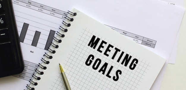 Text meeting goals on the page of a notepad lying on financial charts on the office desk. near the calculator. business concept.