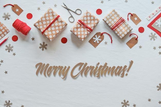 Текст с рождеством. новогодние подарки и украшения ручной работы своими руками. празднование рождества без пластика. подарочные коробки и бирки в крафтовой оберточной бумаге, перевязанные красным хлопковым шнуром.