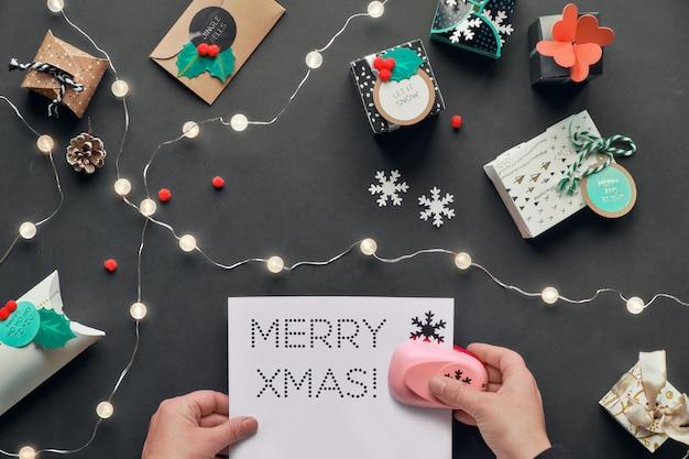 Текст с рождеством на перфорированной бумаге.
