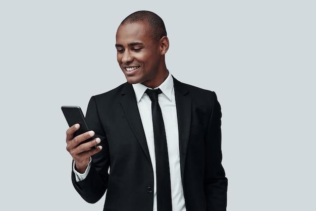 문자 메시지. 스마트 폰을 사용하고 회색 배경에 서서 웃고 있는 정장 차림의 매력적인 젊은 아프리카 남자
