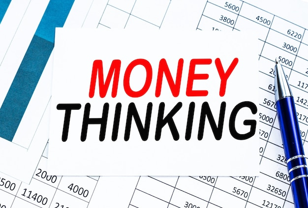 Text money thinking on a white paper over a calendar and a pen by it