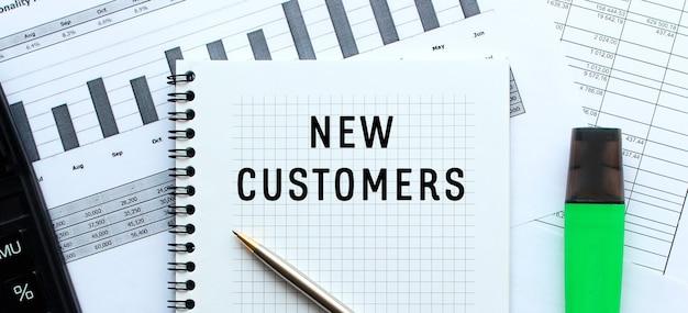 オフィスデスクの財務チャートにあるメモ帳のページで、新しい顧客にテキストメッセージを送信します。電卓の近く。ビジネスコンセプト。