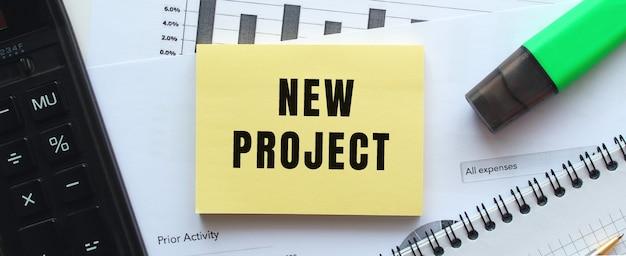 オフィスデスクの財務チャートにあるメモ帳のページに「newproject」とテキストメッセージを送信します。電卓の近く。ビジネスコンセプト。