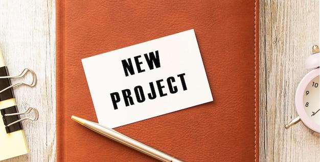 オフィスの机のメモ帳に横たわっている白いカードに新しいプロジェクトをテキストメッセージ