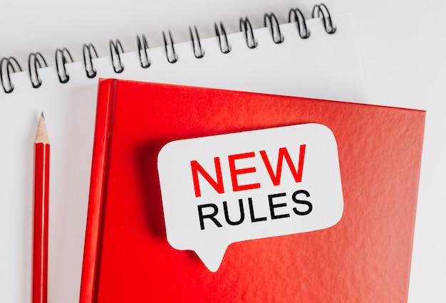 새 규칙은 사무실 문구 배경이 있는 빨간색 메모장에 있는 흰색 스티커입니다. 비즈니스, 금융 및 개발 개념에 평면 누워