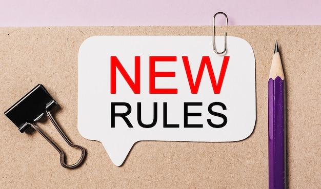 Напишите новые правила на белом стикере с фоном канцелярских принадлежностей. квартира лежала на концепции бизнеса, финансов и развития