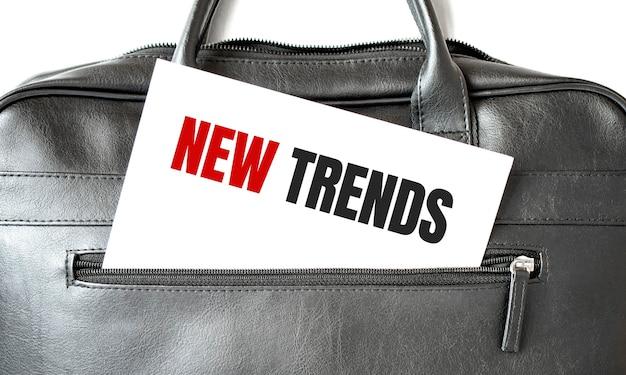 검은 색 비즈니스 가방에있는 백서 시트에 쓰는 새로운 트렌드를 텍스트로 표시합니다.