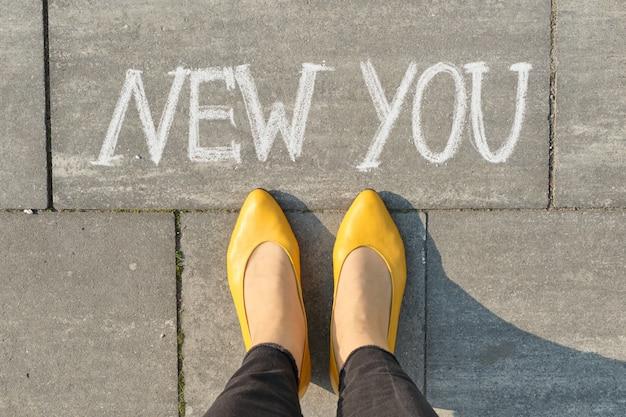 あなたが女性の足で灰色の歩道に書いた新しいテキスト