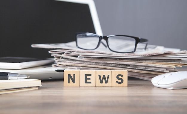 新聞と眼鏡が付いている木製の立方体のテキストニュース。