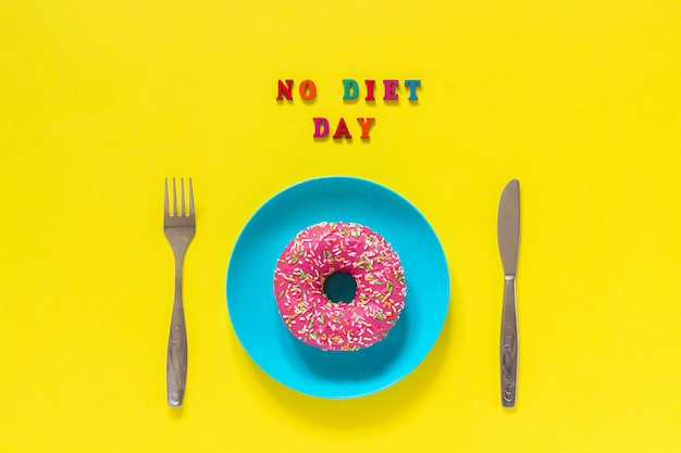 Text no diet day, donut on plate and cutlery table knife fork .