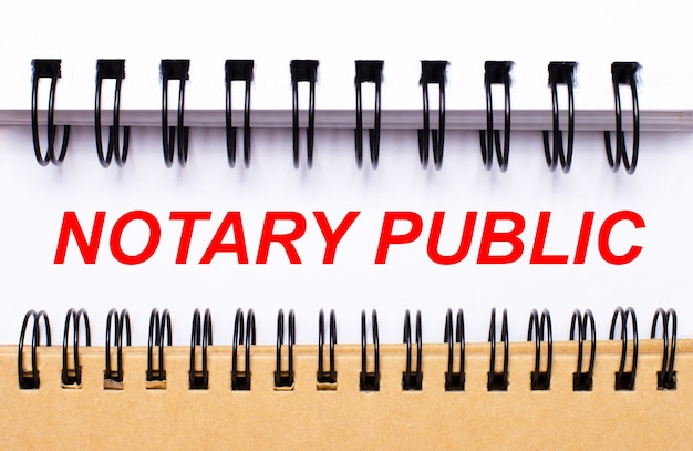 Text notary public on white paper between white and brown spiral notepads.