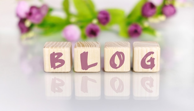Текст слова блог на деревянных кубиках у светлого деревянного стола