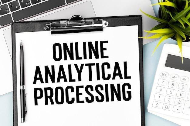 クリップボード、ペン、ラップトップ、電卓、プラントでのテキストオンライン分析処理。ビジネスコンセプト。フラットレイ。