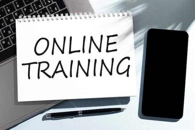 ノートブック、ラップトップ、ペン、携帯電話でテキストオンライントレーニング。