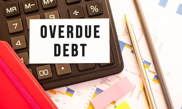 금속 펜, 계산기 및 금융 차트와 흰색 카드에 텍스트 연체 부채. 비즈니스 및 금융 개념