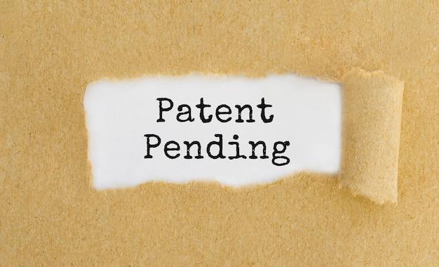 破れた茶色の紙の後ろに表示されるテキスト特許出願中。