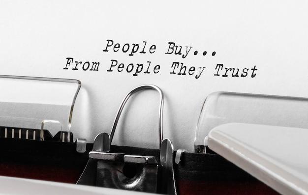Текст, который люди покупают у людей, которым они доверяют, набран на пишущей машинке в стиле ретро.