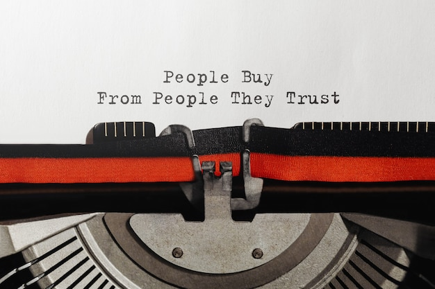 Текст, который люди покупают у людей, которым они доверяют, набран на пишущей машинке в стиле ретро
