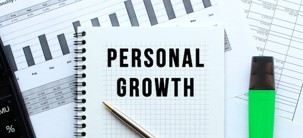 Text personal growth on the page of a notepad lying on financial charts on the office desk.