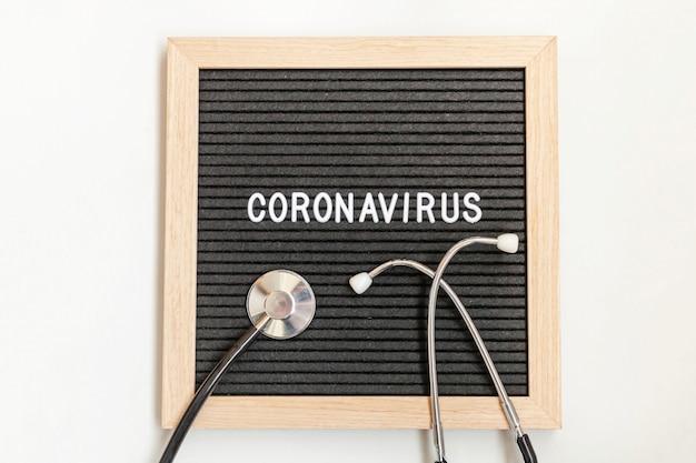 Text phrase coronavirus and stethoscope on black letter board