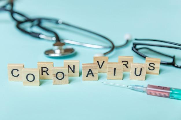 テキストフレーズコロナウイルス注射器眼鏡と青いパステル壁に聴診器。新しいコロナウイルス2019-ncov mers-cov covid-19中東呼吸器症候群コロナウイルスウイルスワクチンのコンセプト。