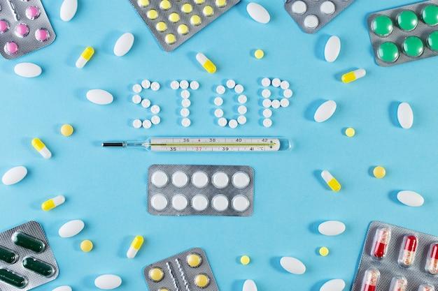 Текстовая фраза стоп на синем фоне с таблетками. различные лекарства в таблетках, медицинском ртутном термометре и шприце. концепция медицины. блистерная упаковка фармацевтическая. пакет таблеток с таблетками.