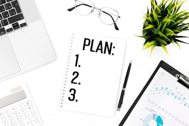 カードにplanとテキストメッセージを送信します。ノートパソコン、電卓、チャート用クリップボード、メガネ、ペン、オフィスの机の上の植物。フラットレイ、上面図。計画コンセプト。