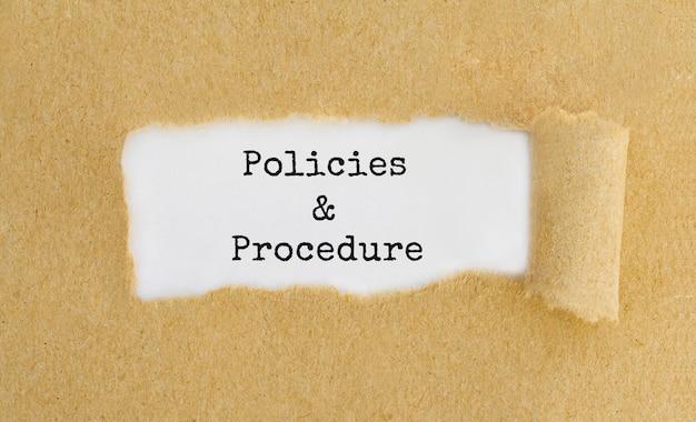 찢어진 갈색 종이 뒤에 나타나는 텍스트 정책 및 절차.