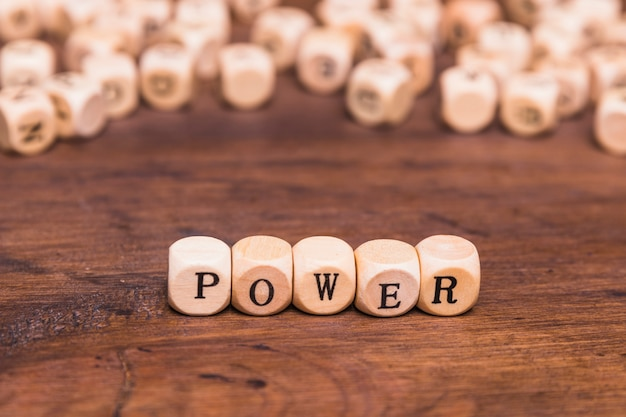 Text power written on wooden dices over brown desk