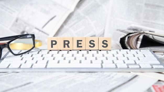 コンピューターのキーボード、新聞、眼鏡を使って木製の立方体をテキストで押します。